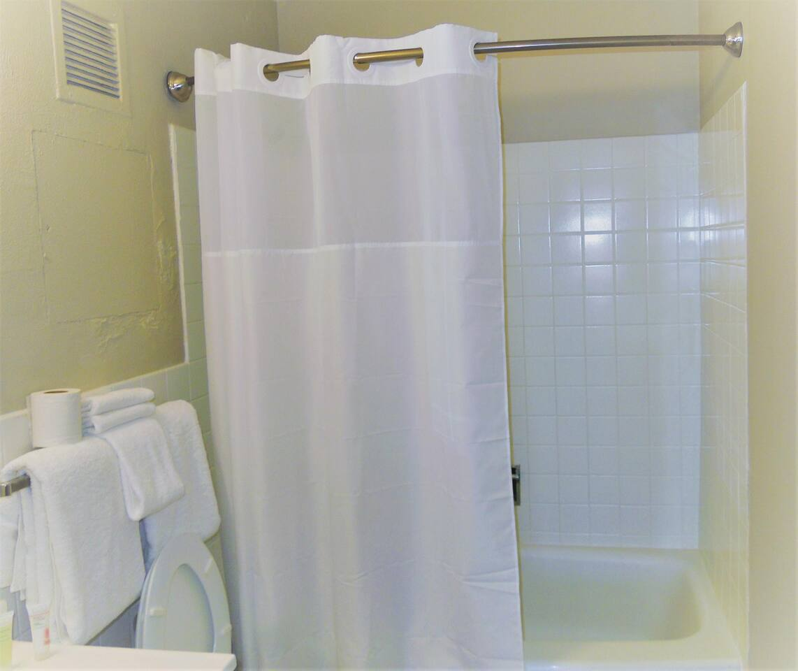 Bathroom featuring tub and complimentary travel size soap and shampoo