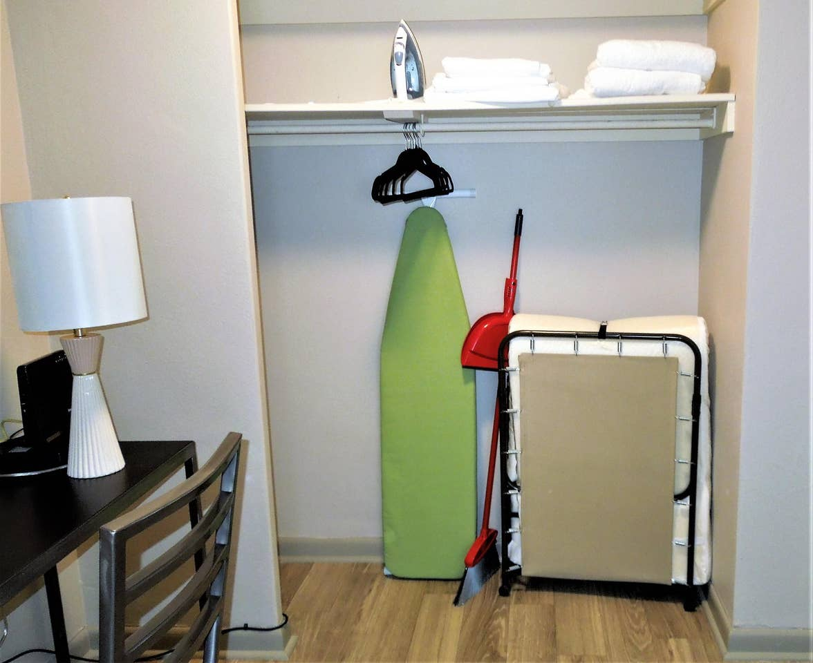 Closet featuring: Ironing Board, twin sized cot & hangers
