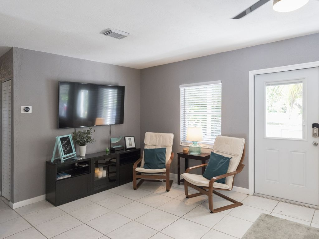 Family living room with 2 side rocking chairs, large flat screen tv