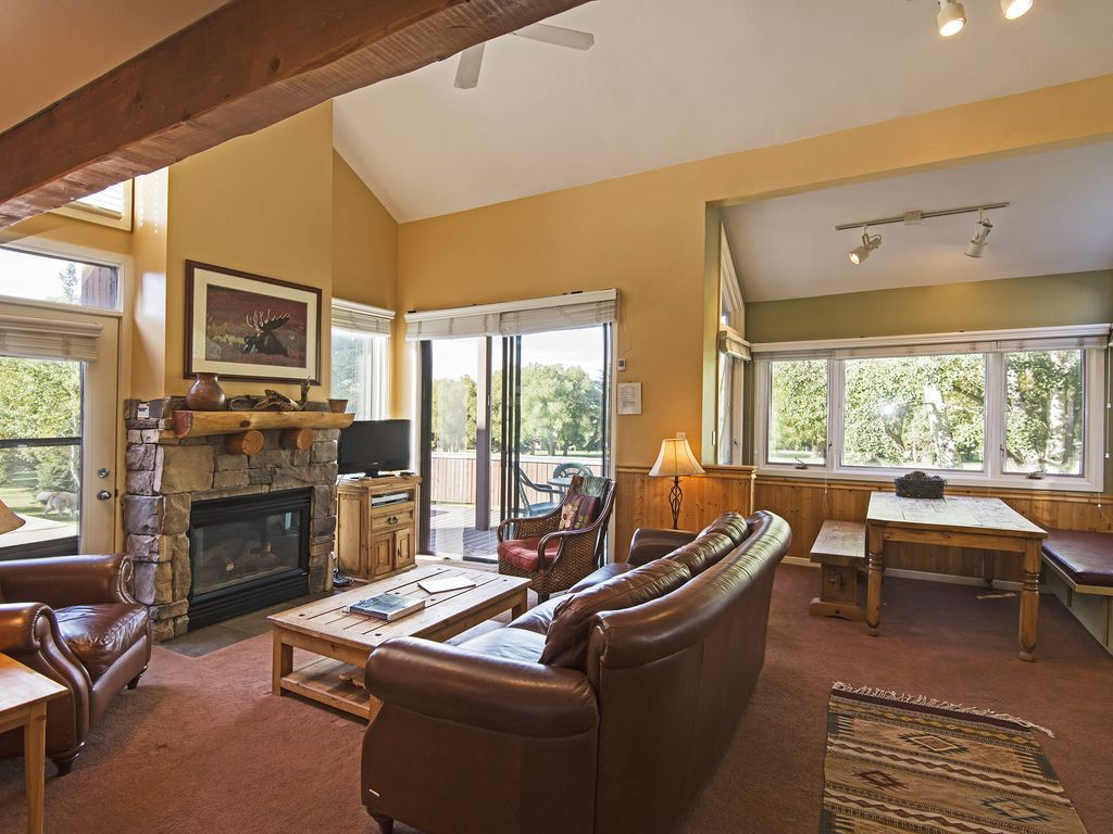 Living room, dining, and walk out to deck that looks over golf course