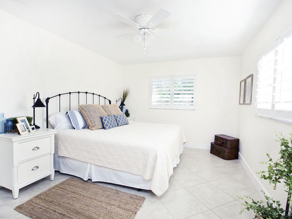 Grosses Schlafzimmer mit hochwertiger Bettwäsche und Plantation Shutters.