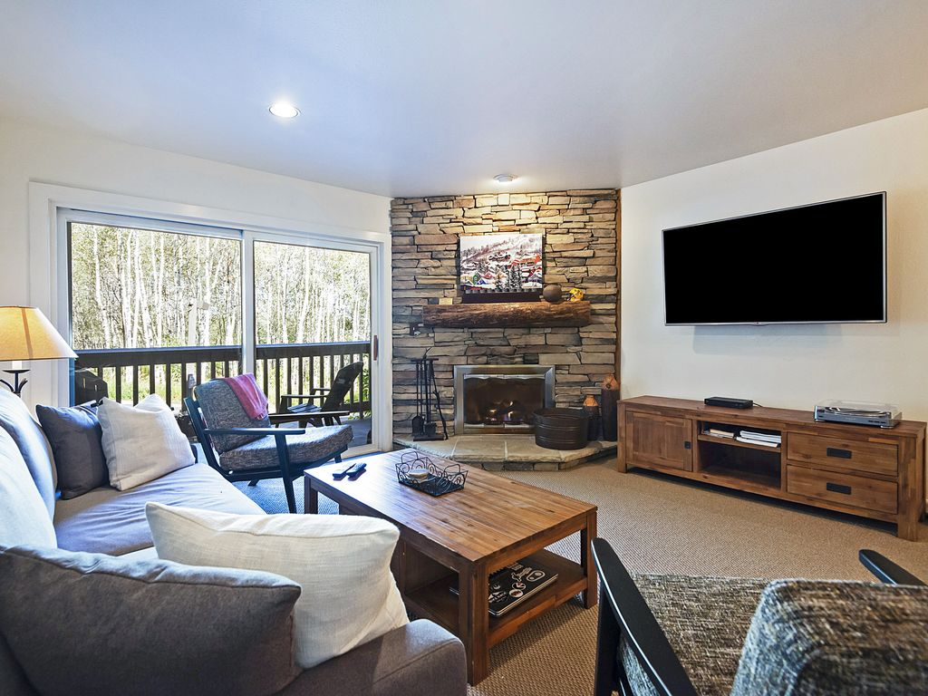 "Living area with 72"" flatscreen, wood fireplace, private deck, sleeper sofa"