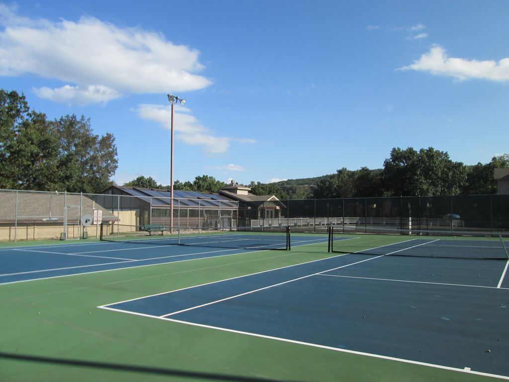 The tennis courts are lit at night. The indoor pool is in the background.