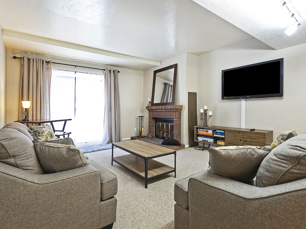 Living area with wood burning fireplace, flat screen TV, queen sleeper sofa