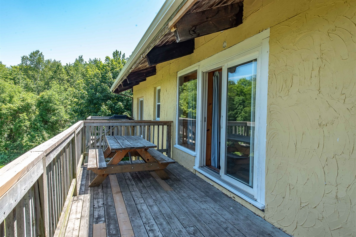 Oversize balcony for outdoor barbecuing and dining with view of backyard and forest