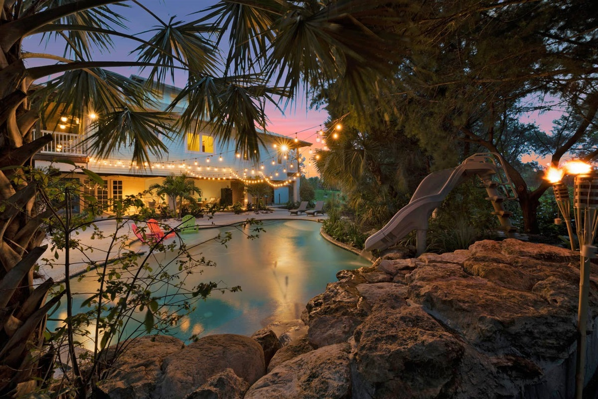 SUNSET VIEW OF THE POOL,SLIDE , DECK AREA AND  LANAI.