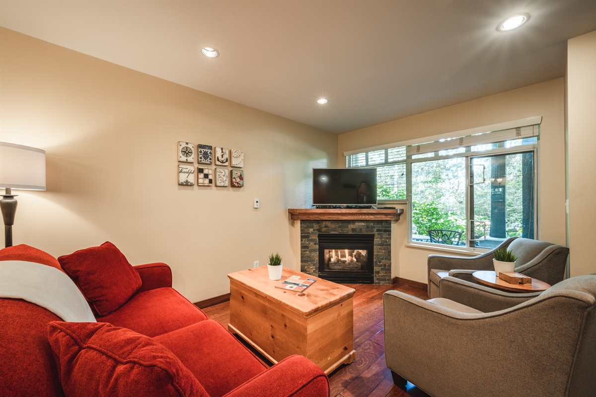 Living Room - Cozy fireplace, SmartTV, large window onto patio, comfortable sofa and lounge chairs.
