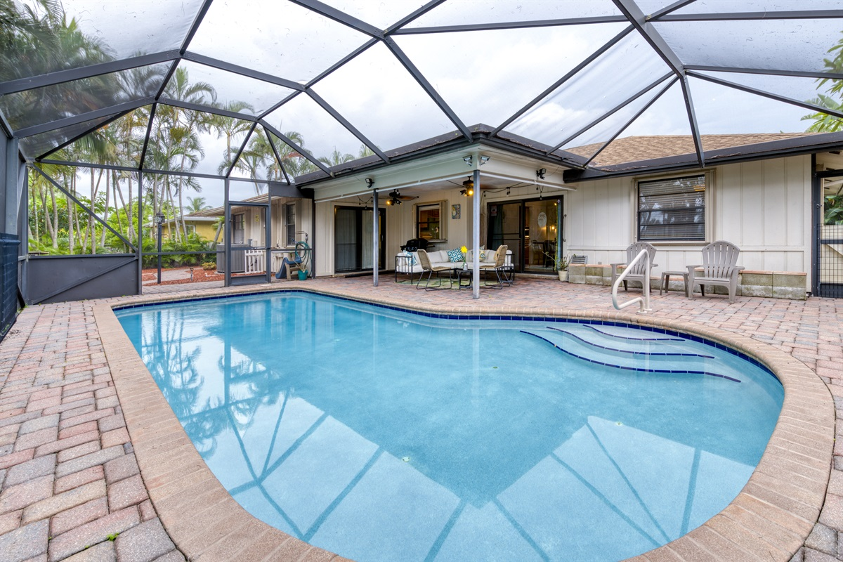 Gorgeous screened in pool with BBQ grill and outdoor lounge seating. Overlooking the Golf Course
