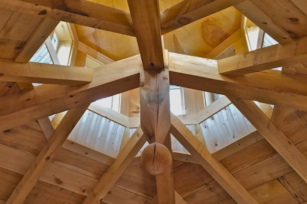 Looking up from the bed- the cupola with a vintage ships light. Beautiful timberframing and a significant architectural detail.