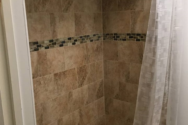 TUB / SHOWER  Shower feature tub to ceiling tiles.