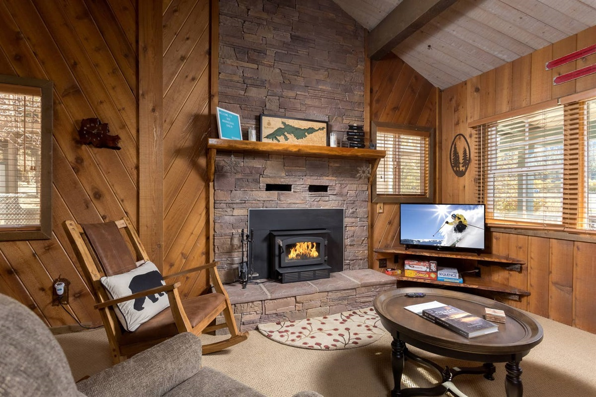 Cozy living room with a floor-to-ceiling rock (wood burning) fireplace, TV with Roku, sitting area with sofa, & rustic charm!