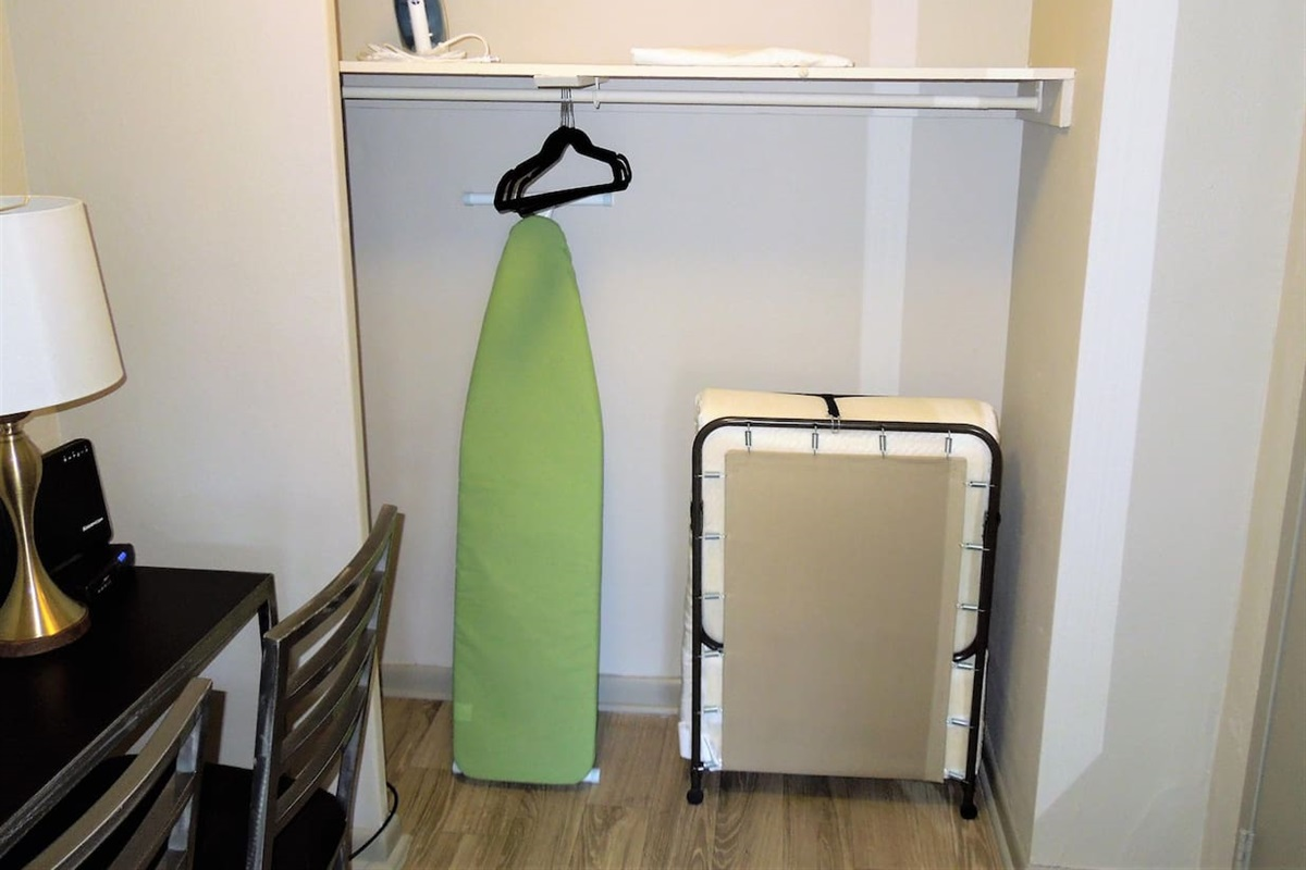 Closet with ironing board and iron. Twin size cot available for additional sleeping arrangements