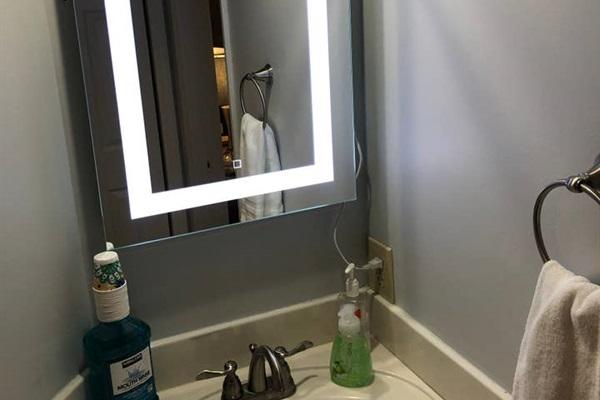 Bathroom features backlit vanity mirror.