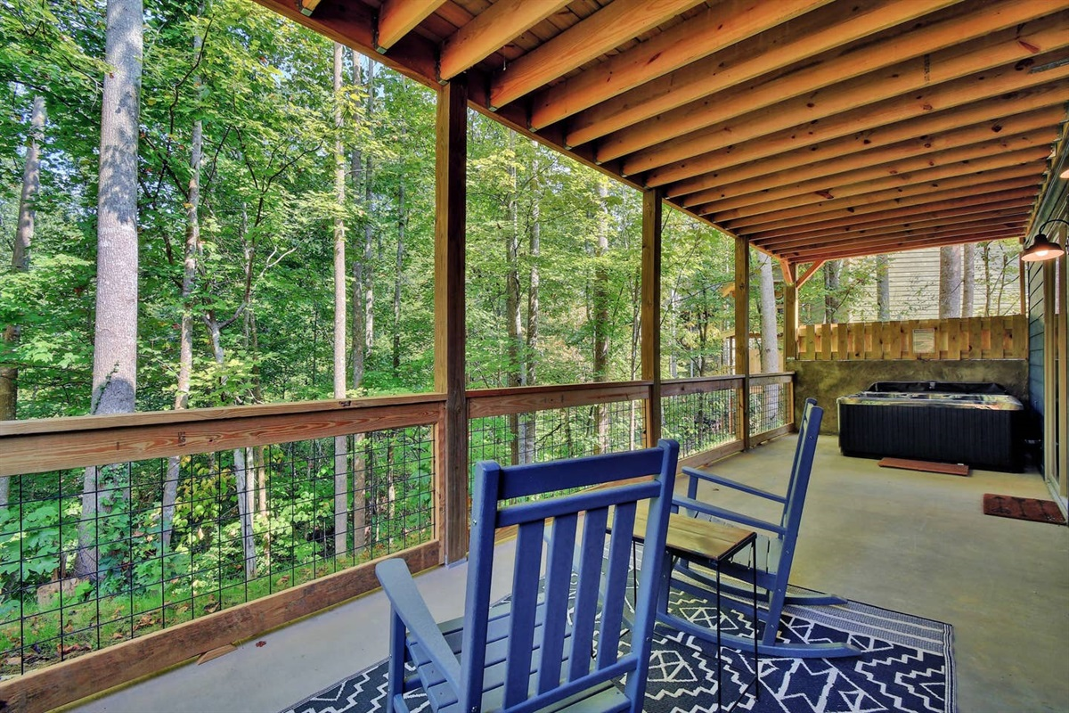 The lower level deck with seating and a hot tub