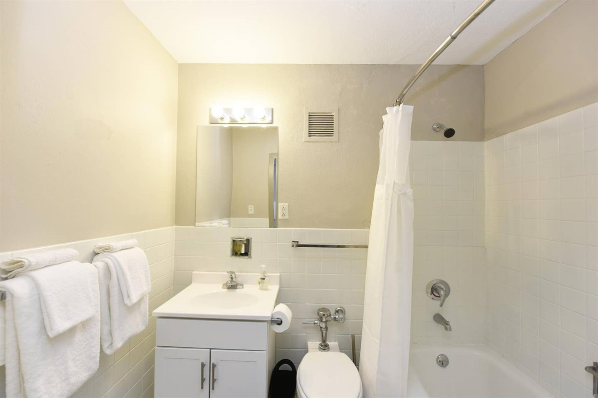 Bathroom equipped with tub & complimentary travel size soap & shampoo.