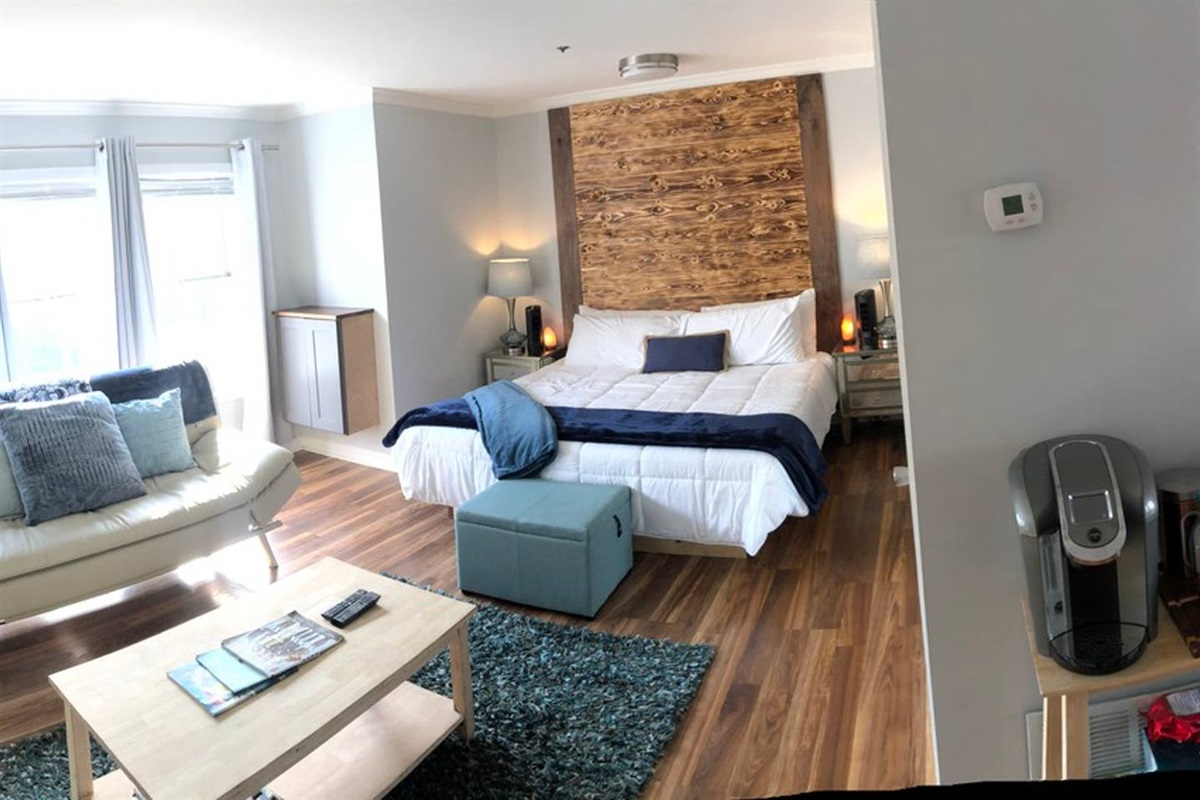 PANARAMA VIEW: (From left to right)  >Door leading to 2nd Ave gate. >TV & Coffee Table > Sleeper couch >Window view to 2nd Ave >King Bed > Door to bathroom >Coffee station >Kitchen >Doors facing gated courtyard & parking