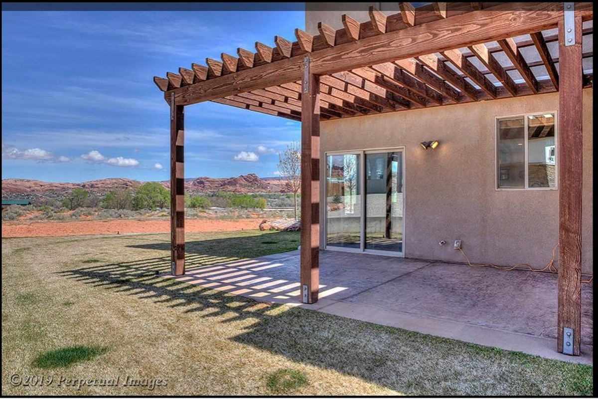 Covered private patio and green lawn