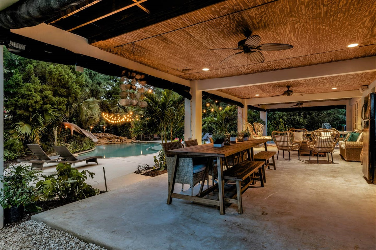 SUNSET VIEW OF LANAI  AREA WITH OUTDOOR GRILL, REFRIGERATOR, DINING TABLE, SEATING AREAS AND SWING RIGHT OFF THE POOL AND FRONT YARD FOR OUTDOOR FUN AND GATHERING.