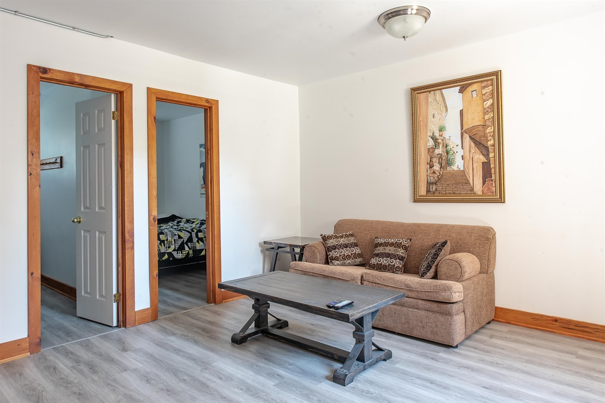"""Lower level living room with couch and 55"""" 4K TV"""