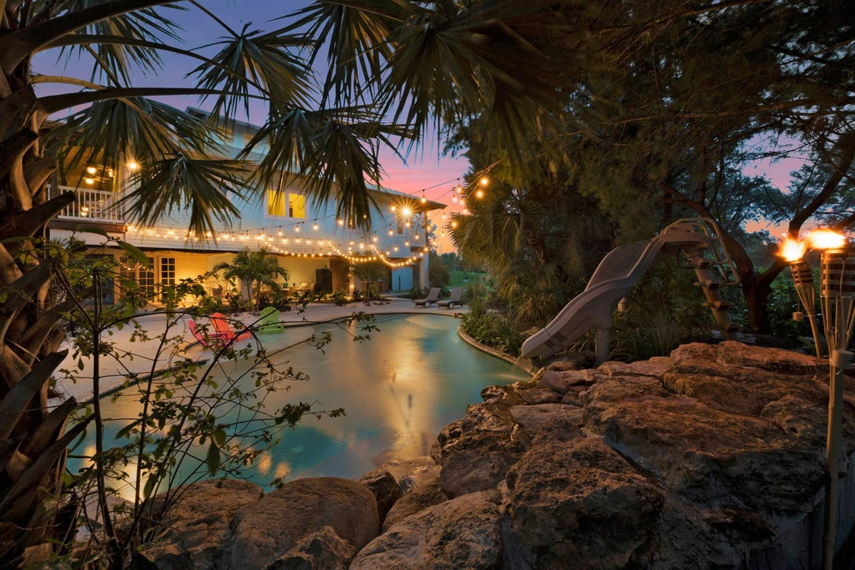 SUNSET VIEW OF THE POOL FROM BEHIND THE WATERFALLS.