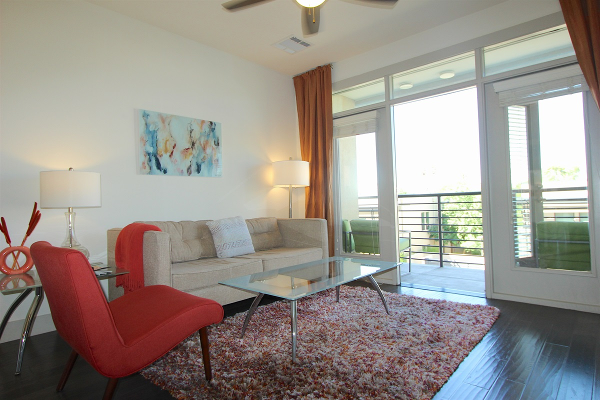 Living area with comfy couch, side chair & spacious patio.