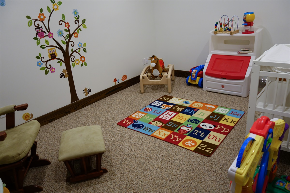 Dedicated nursery room with changing table, glider and toys