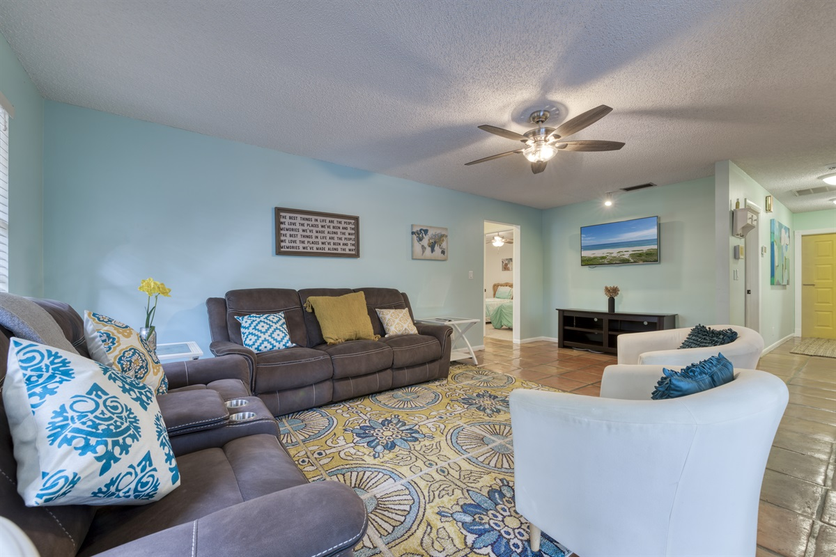 Warm and inviting living room with reclining sofas, large TV with Roku to stream your favorite shows and entrance to the outside patio and pool area.