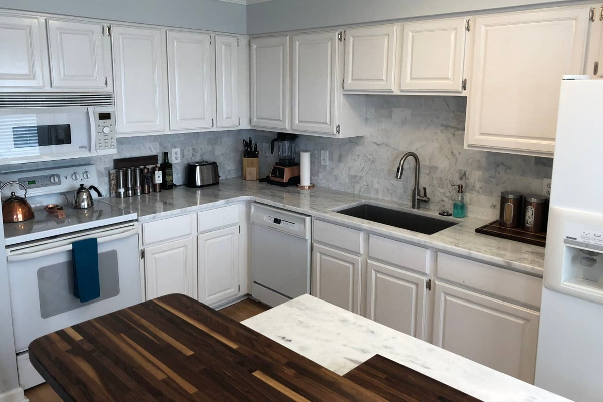 FULL KITCHEN  Cook meals with ample counter space to prepare food in the kitchen that features full size appliances: refrigerator, electric stove, built-in microwave, and dishwasher.