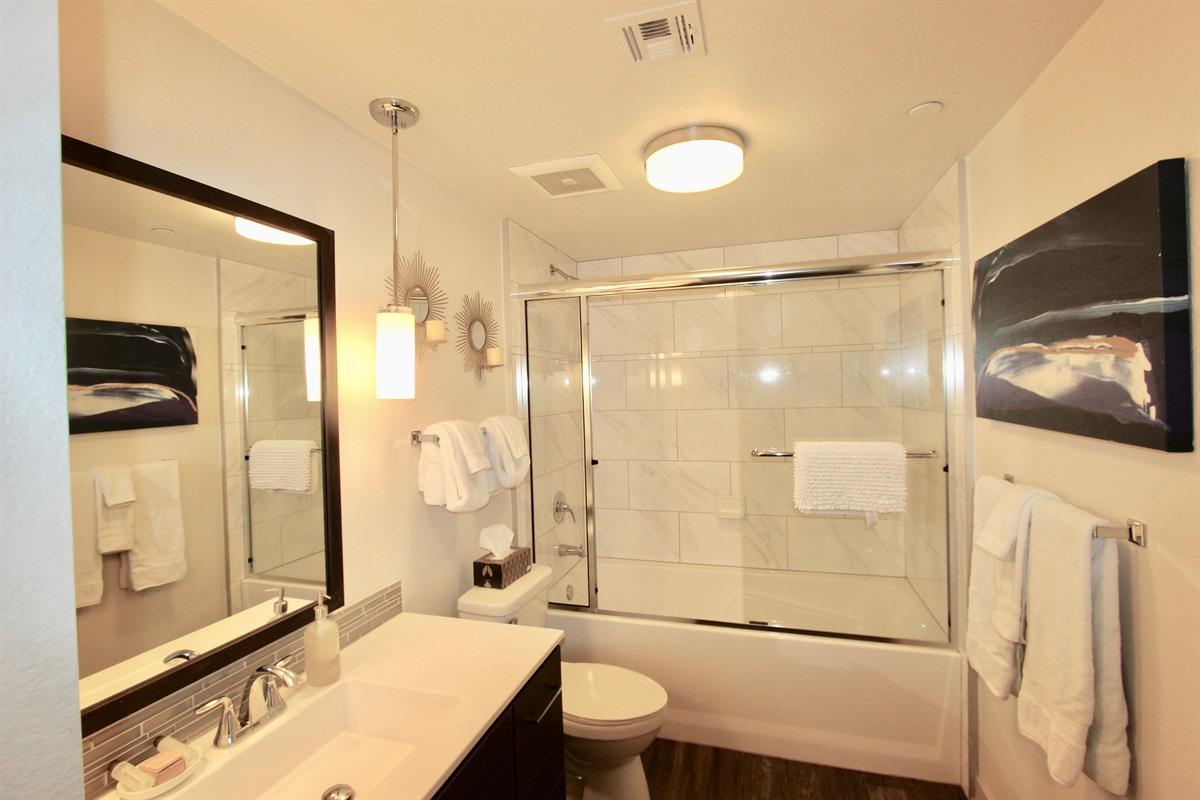 Bathroom with quartz counter, tub/shower enclosure.